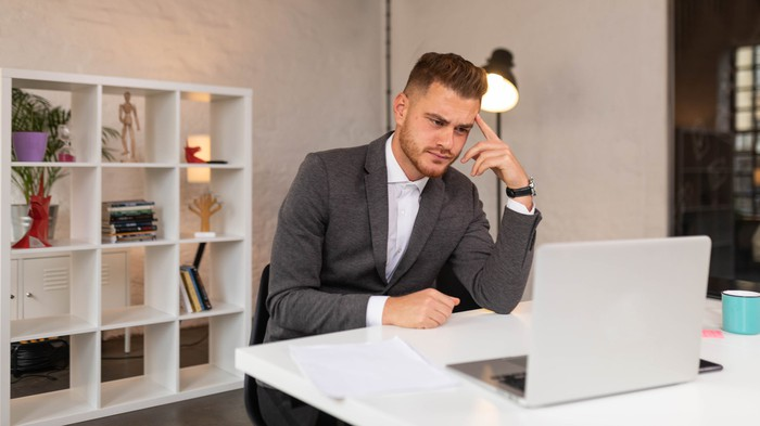Businessperson at desk looking at laptop with skeptical expression.