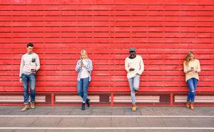Quatre personnes debout contre un mur utilisant des smartphones.