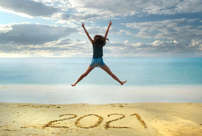 A woman jumping up in the air with 2021 written on the beach sand.