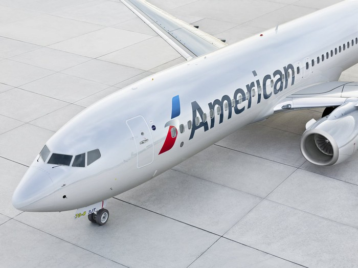An American Airlines commercial plane outside of a terminal gate.