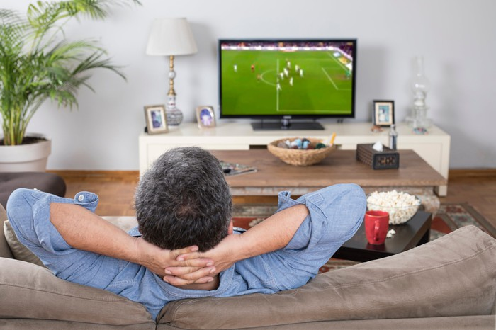 Man in a sofa watching a soccer match on TV.