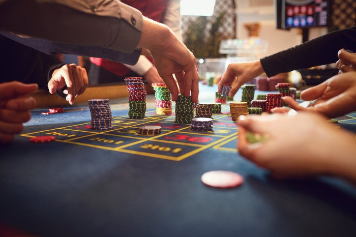 Gamblers placing chips on a roulette table.
