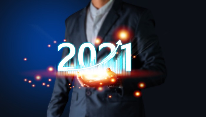 A man holding a tablet displaying a chart and the number 2021.