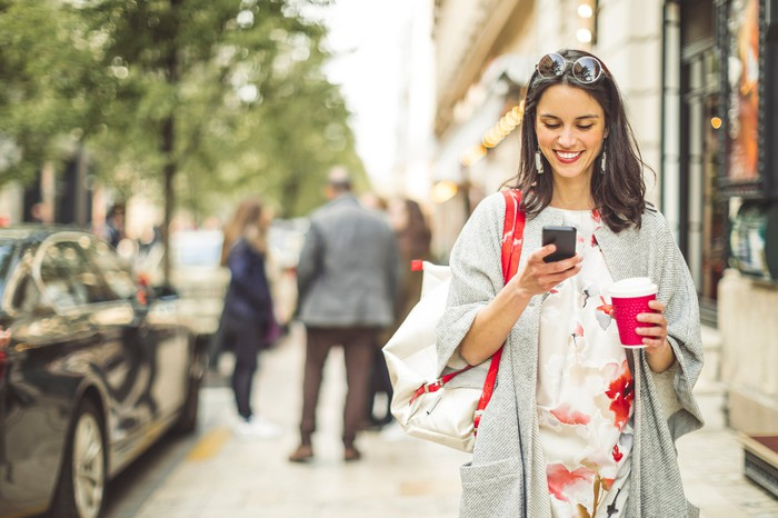 A woman holding a coffee, looking at her phone, smiling as she walks down the street.