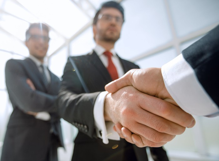 Two businesspeople shake hands as one watches approvingly in the background.