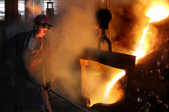 A steel worker in a foundry with molten steel pouring from a vessel.