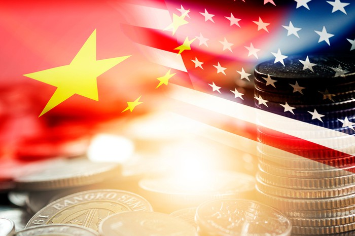U.S. and China flags superimposed above a picture of coins.