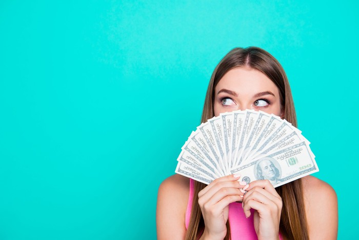 Woman holding fan of cash in front of face