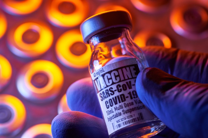 A researcher's hand holds a vial of coronavirus vaccine against a gold and purple background.