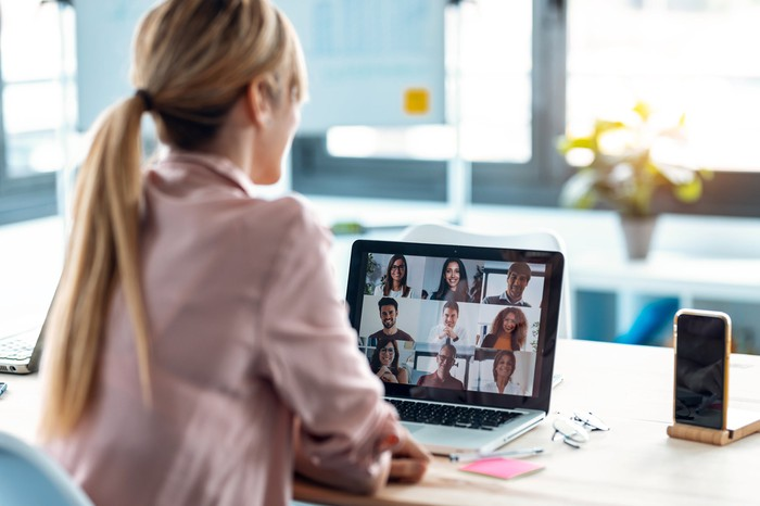 Woman on video meeting with nine others.