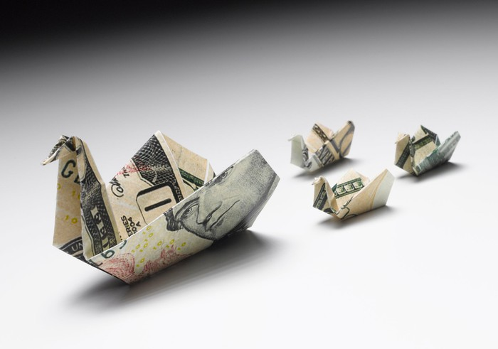 Money folded into an origami duck and three baby ducks following