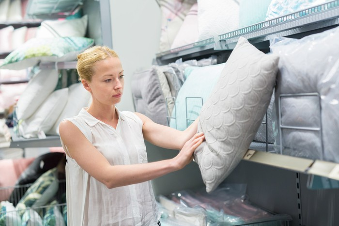 A woman looking at a pillow in a store