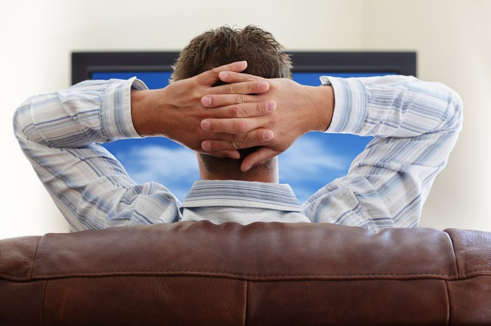 A relaxed man sits on a couch while watching TV.