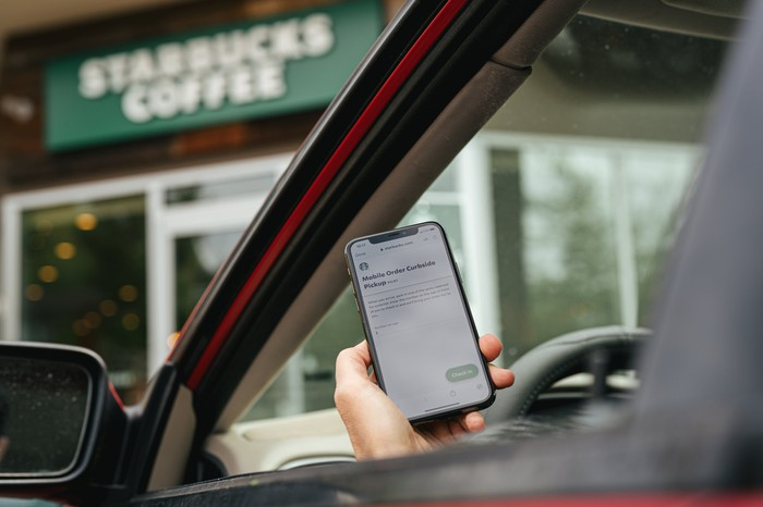 Starbucks store facade seen from a car occupied by person using the company's mobile app.