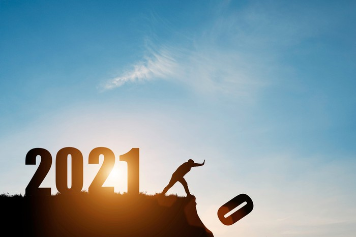 A person pushes the number zero down the cliff that has the number 2021 with blue sky and sunrise.