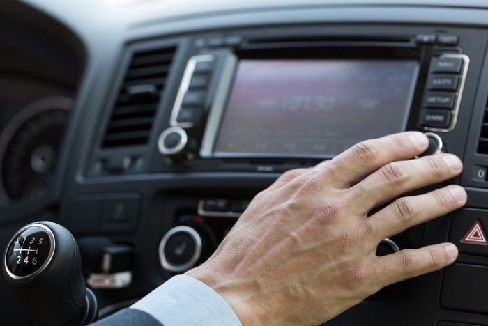 A man's hand working the controls on a car radio.