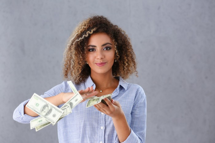 A smiling young woman is scattering a pile of hundred-dollar bills from her hand.