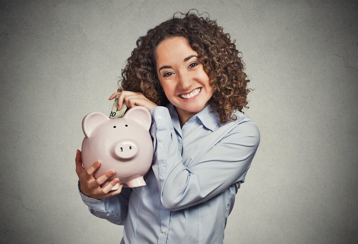 Smiling woman depositing money into piggy bank.