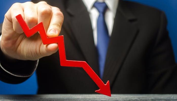A businessman holds a declining arrow.