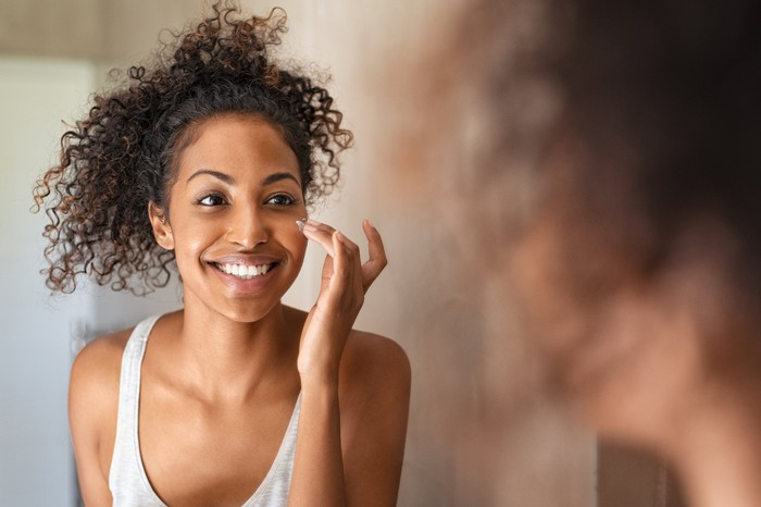 A young woman applies moisturizer to her face.