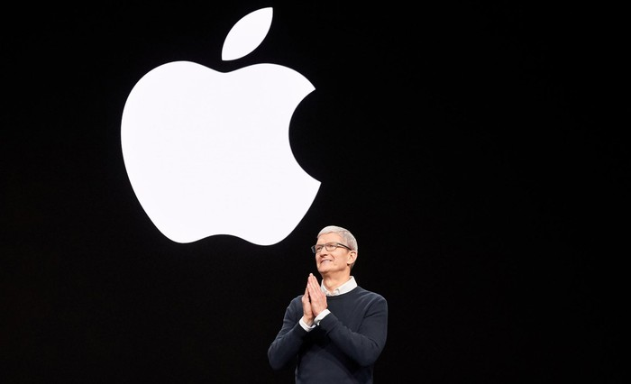 Tim Cook presenting onstage with large Apple logo behind him
