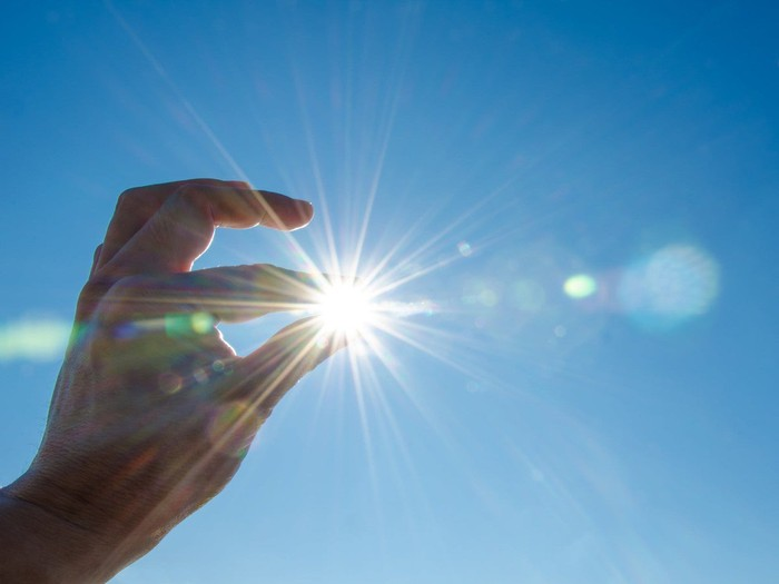 Hand with fingers positioned to appear to grip the sun.