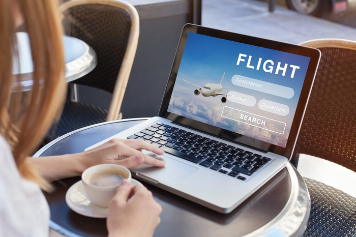 woman booking travel flight online at a coffee shop