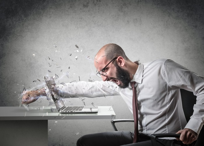 A businessperson driving a fist through a laptop screen.