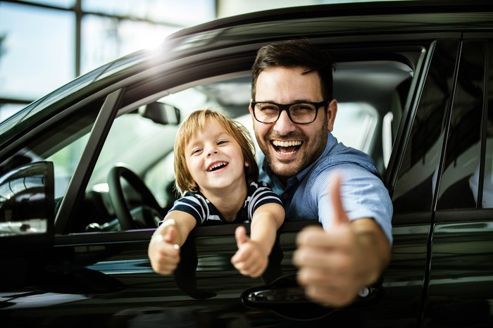 Parent and child in the driver's seat of a car, smiling and giving the thumbs-up.