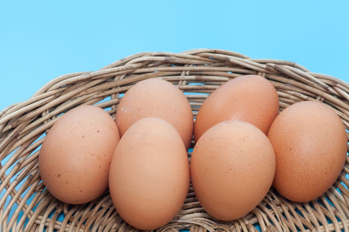 Six brown-shelled eggs in a basket with a blue background.