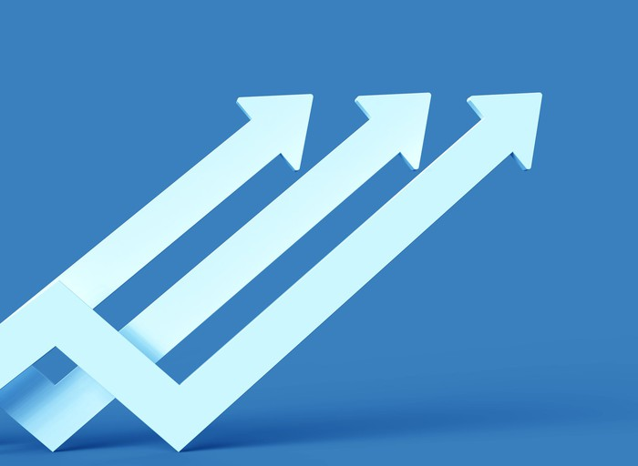 Three white arrows trending up with a blue background