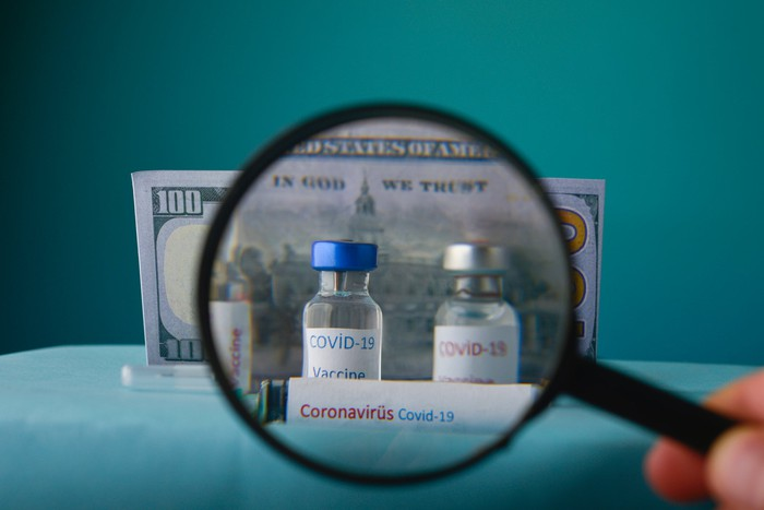 Magnifying glass in front of two COVID-19 vaccine vials with a $100 bill behind them