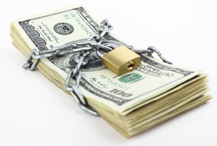 Stack of cash secured with a padlock.