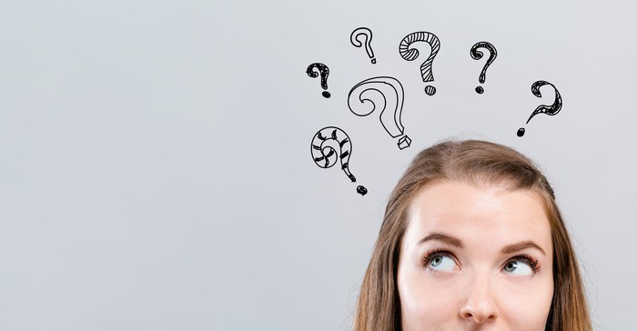 Woman looking up at question marks hovering above her head.