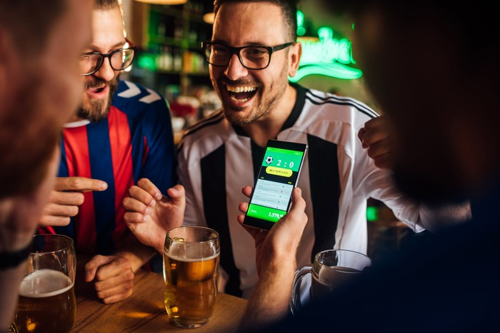 People drinking beer and using a sports betting app on a mobile phone.