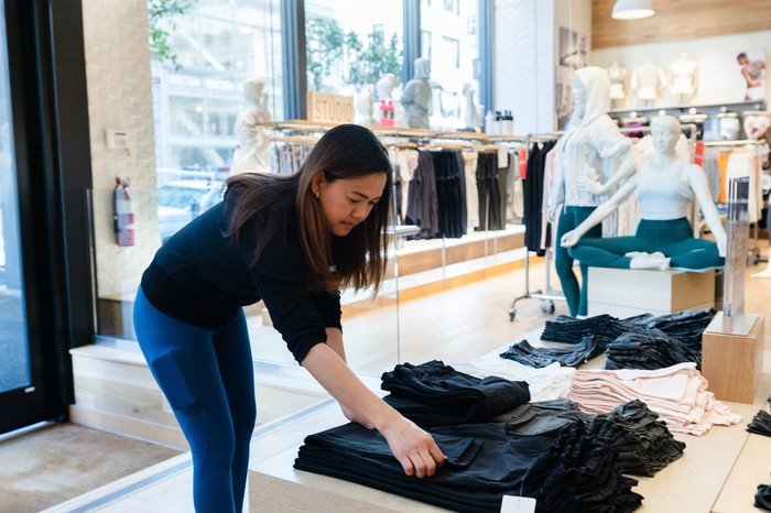 Athleta salesperson fixing clothes in a stores.