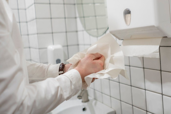 Person drying hands with tissue paper while standing beside a tissue dispenser