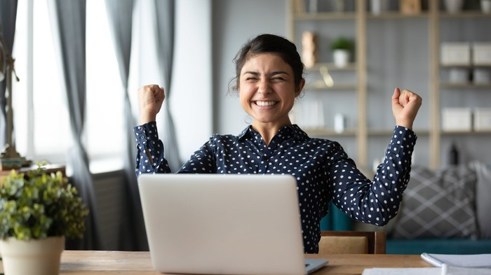 A young woman celebrates behind a laptop screen.