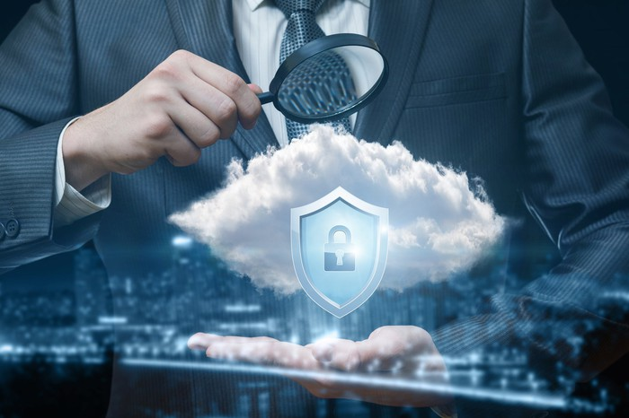 Man in suit looking at cloud with lock icon through magnifying glass