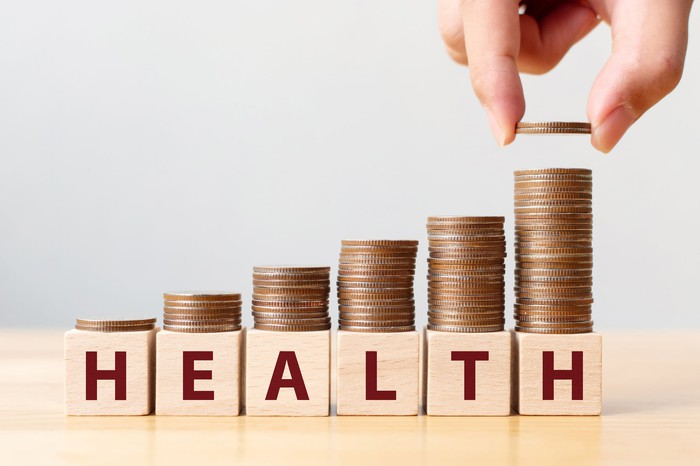 "An investor's hand places coins on top of blocks spelling ""health."""