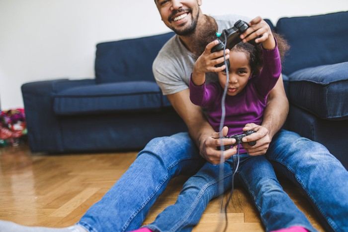 father and daughter sitting on floor playing video games