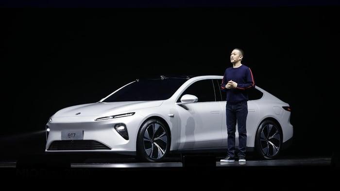 Li is on stage with a white ET7, a sleek sedan.