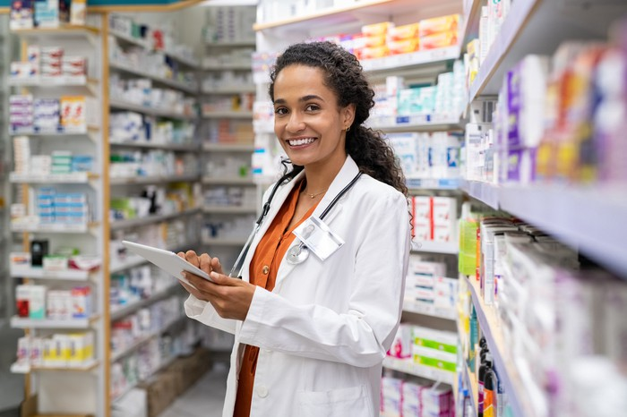 Female pharmacy employee wearing stethoscope, white coat, and badge holds a clipboard standing in between shelves of medication
