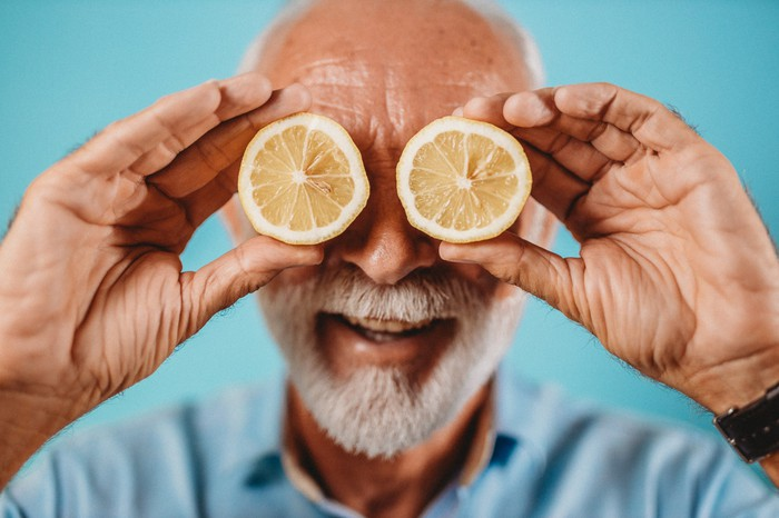 Man holding cut lemons over his eyes and smiling.