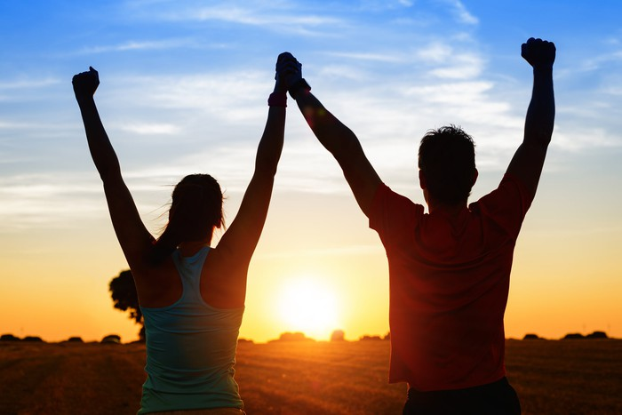 Silhouette of two people joining hands to celebrate together as the sun rises at the horizon.