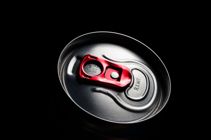 The illuminated top of an energy drink can against a dark background, with a red pull tab.