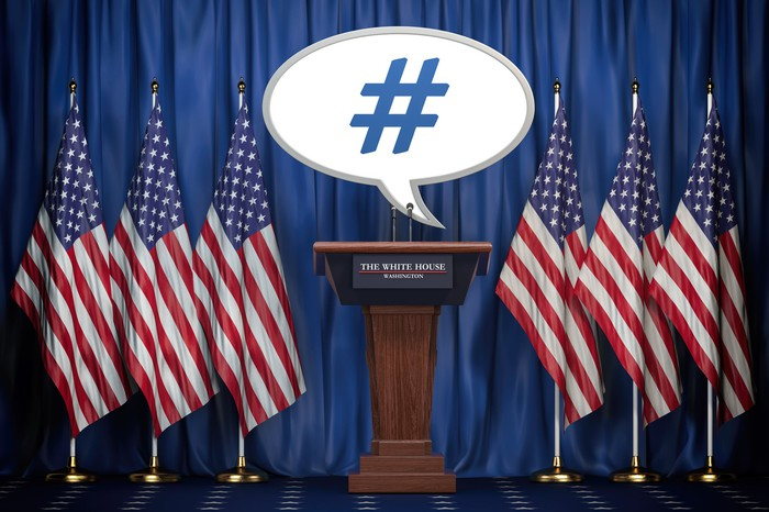 A speech bubble containing a hashtag is at a lectern with the words The White House labeling it and surrounded by American flags.