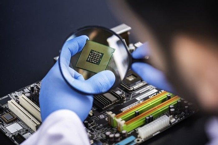 A lab technician examines a semiconductor chip with a magnifying glass.