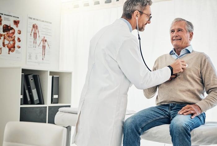 Doctor listening to older man's heart
