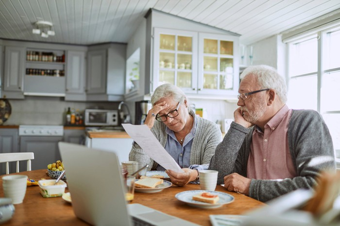 Older couple at table with food and laptop in front of them looking at document